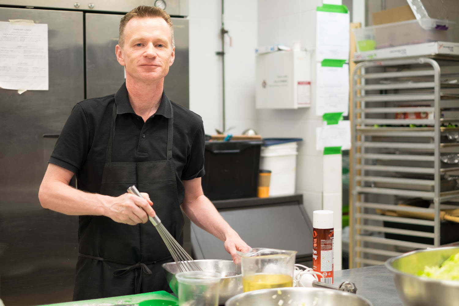 Stephen wearing a black shirt and apron whisking in a kitchen with kitchen equipment in the background. Stephen is looking at the camera and smiling.
