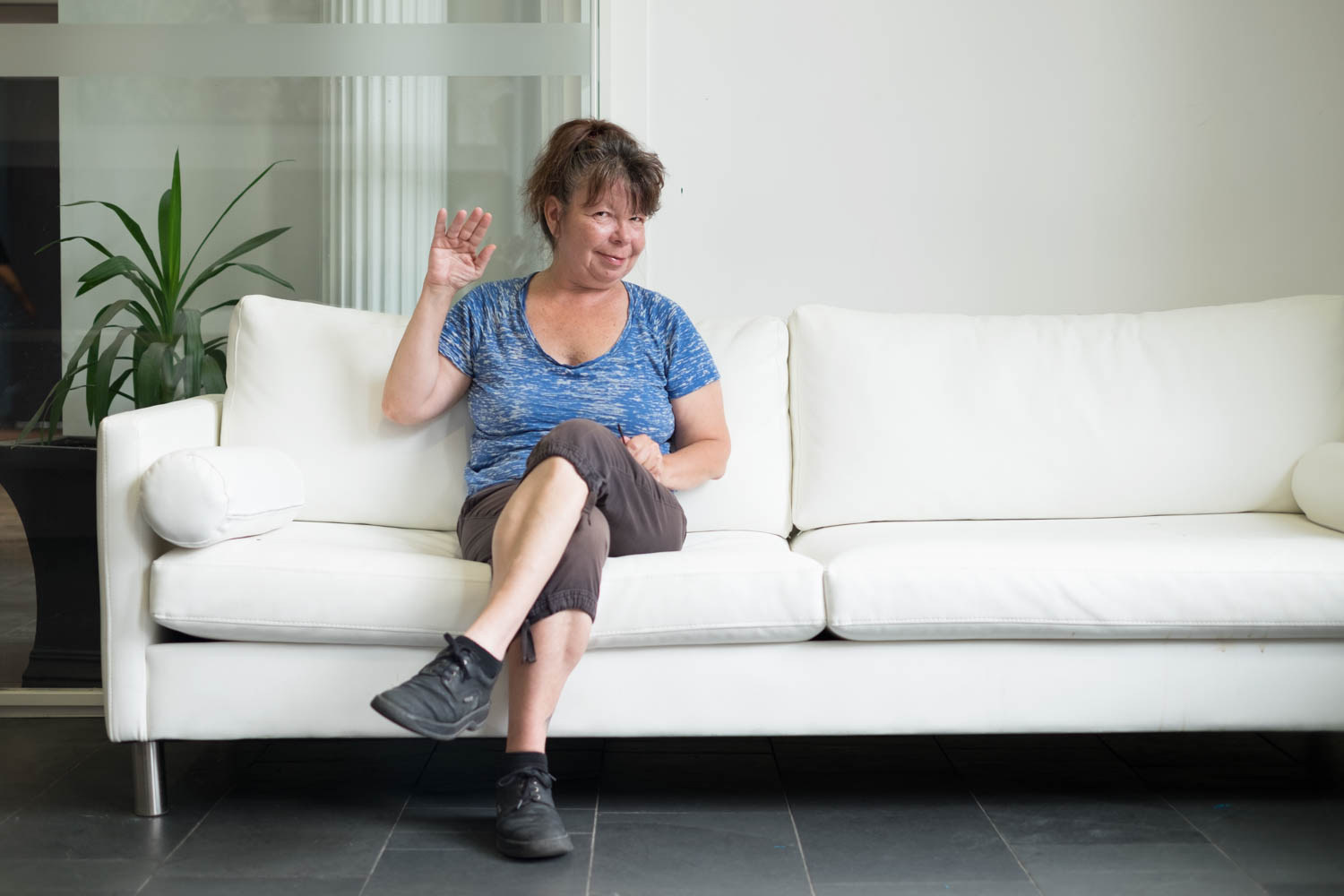 Colleen wearing a blue T-shirt, brown capris, and black laced shoes sitting on a white couch and waving to the camera. Colleen has their hair in a pony tail  and there is a white pillar and a potted plant in the background.