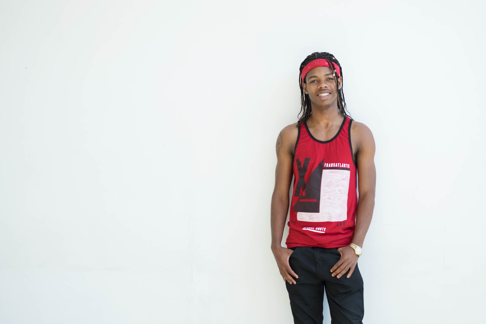 Justin standing against a white background with their hands in their pockets. Justin is wearing a red tank top with black and white screen print, black pants, and a red head band. Justin has braided hair and is smiling at the camera.