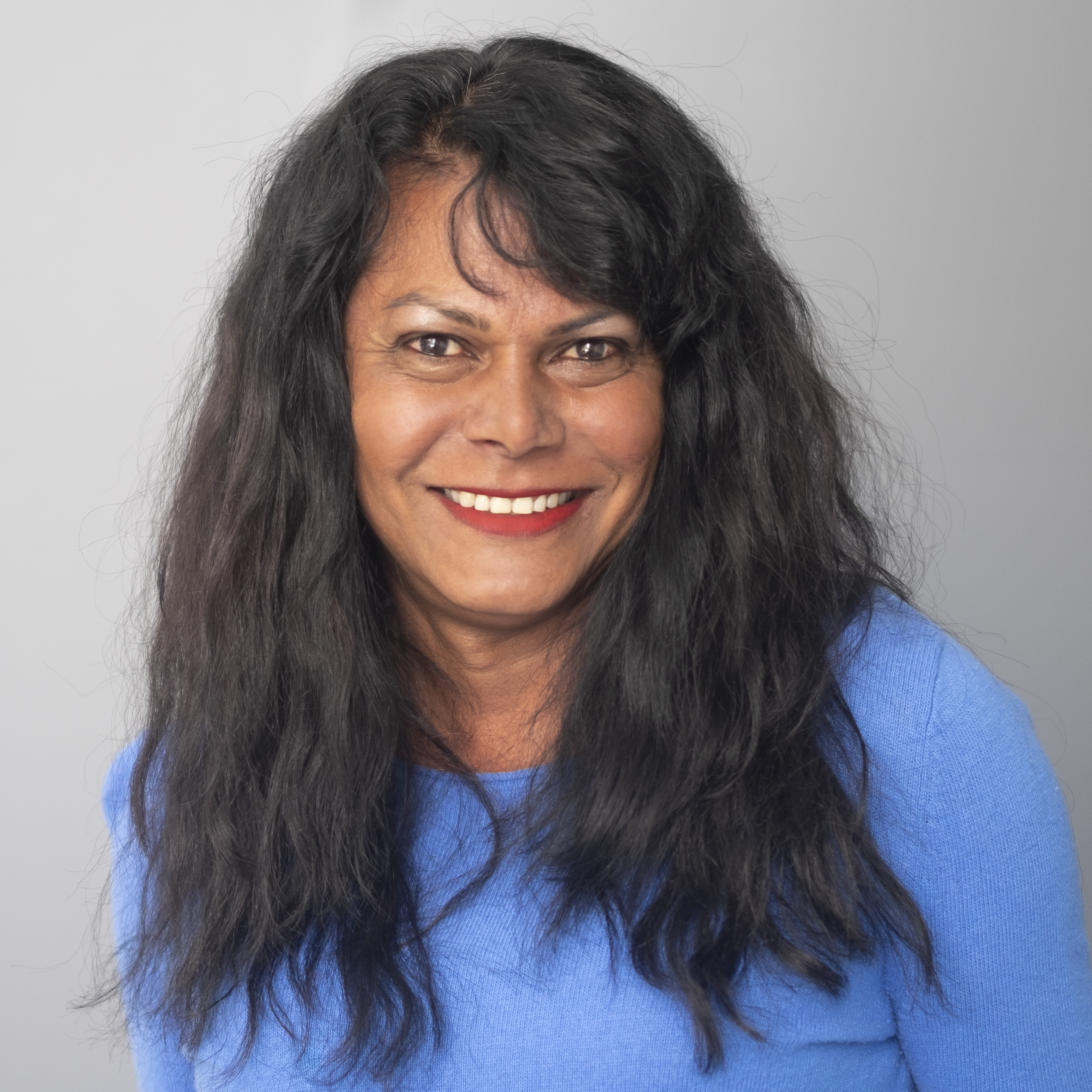 Yasmeen Persad's smiling portrait, wearing blue shirt against grey background.